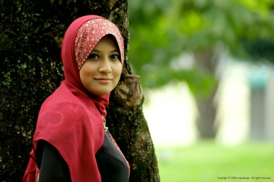 Muslim woman wearing a red hijab, a scarf the covers a woman's hair and neck.